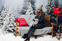 Woman in gray sitting on bench among christmas tree. royalty free stock photos
