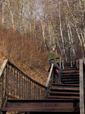 A woman in gray skirt and pantyhose, wearing a green hat, is sitting on the railing of a long staircase. A woman in a gray skirt and pantyhose, wearing a green royalty free stock photography