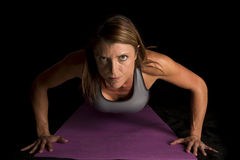 Woman gray sports bra on black push up. A woman doing a push up on her fitness mat stock photos