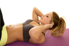 Woman gray sports bra lay doing crunch from side Stock Image