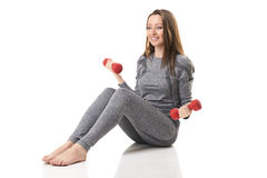 Woman in gray sports thermal underwear makes exercises with red dumbbells in sitting position. Stock Image