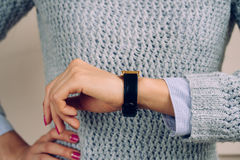 Woman in a gray sweater checks the time on a wrist watch close-up Royalty Free Stock Image