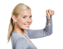 Woman keeps a key. Woman in gray sweater keeps a key, isolated on white Stock Photos