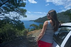 Woman in Gray Tank Top Beside White Car Near Body of Water Royalty Free Stock Image