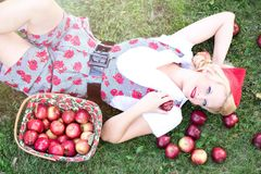 Woman in Gray and White Rose Print Onesies Laying on Grass Beside Red Apple Fruits Royalty Free Stock Image