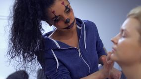 Woman with greasepaint applies foundation on woman`s face in theatre. Professional make-up artist makes a beautiful greasepaint to the actress in theatre. The stock footage
