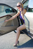 Woman with great legs exit the car Stock Photos