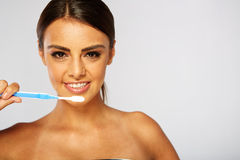 Woman with great teeth holding tooth-brush Royalty Free Stock Photography