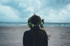 Woman With Greed Headdress Facing Towards Beach Under Blue Sky Stock Image