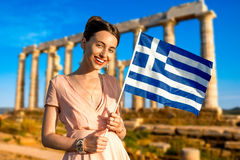 Woman with Greek flag on ancient ruins background Stock Photos
