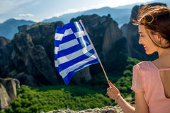 Woman with greek flag. Young woman in the pink dress with greek flag at the mountains near Meteora monasteries in Greece stock photo