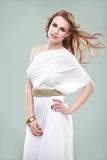 Woman in greek inspired white dress, smiling,. A studio portrait of a beautiful young woman, wearing a long, white, ancient greek inspired dress, smiling, with Royalty Free Stock Images