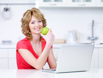 Woman with green apple and laptop Royalty Free Stock Images