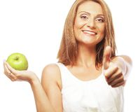 Woman with green apple and showing thumb up. Young woman with green apple and showing thumb up Royalty Free Stock Photos