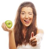 Woman with green apple and showing thumb up. Young woman with green apple and showing thumb up Royalty Free Stock Photo
