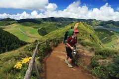 Woman with green backpack walking on the trail leading to the Green and Blue Lakes, Sao Miguel Island royalty free stock photos