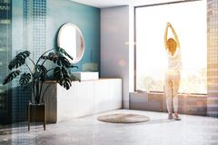 Woman in green bathroom corner with sink. Woman in corner of modern bathroom with dark green walls, concrete floor, sink standing on white countertop and round royalty free stock photos