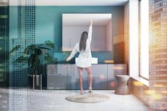 Woman in green bathroom interior with sink. Woman in interior of modern bathroom with dark green walls, concrete floor, sink standing on gray countertop and stock image
