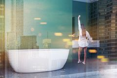 Woman in green bathroom interior, white tub. Woman standing in modern bathroom corner with green walls, concrete floor, white bathtub and a sink with round royalty free stock images