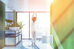 Woman in green bathroom, sinks and toilet. Woman in interior of panoramic bathroom with green walls, white marble floor, a toilet and double sink standing on royalty free stock photos