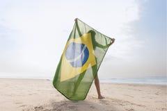 Woman in green bikini holding up Brazil flag on beach. Young attractive woman in green bikini holding up Brazil flag on beach royalty free stock photography