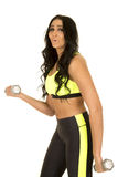 Woman in green and black fitness clothes side weights Stock Images