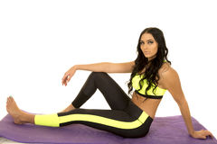 Woman in green and black fitness clothes sit arm on leg Royalty Free Stock Photo