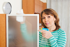 Woman in green cleaning  glass with detergent Royalty Free Stock Photography