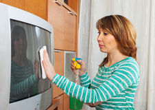 Woman in green cleaning TV with cleanser. At home Stock Photography