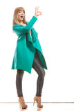 Woman green coat making ok sign Royalty Free Stock Photo