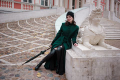 Woman in a green coat posing on stairs. Against the city building in autumn day Royalty Free Stock Images