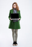 Woman in green coat showing blank laptop computer screen. Full length portrait of a smiling young woman in green coat showing blank laptop computer screen Stock Images
