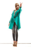 Woman green coat showing victory sign Stock Photos
