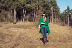 Woman in green coat walks on nature spring Royalty Free Stock Image