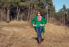 Woman in green coat walks on nature spring Stock Photos