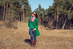 Woman in green coat walks on nature spring Stock Photo