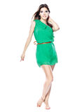 Woman in green dress barefoot Stock Images