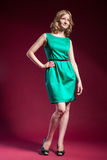 Woman in green dress barefoot on red Stock Photos