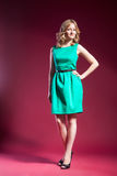 Woman in green dress barefoot on red Royalty Free Stock Images