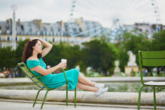Woman in green dress drinking coffee in Tuileries garden of Paris, France. Beautiful young woman in green dress drinking coffee in Tuileries garden of Paris Stock Photography