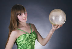 Woman in green dress with gold sphere. Stunning woman in green dress with gold sphere in hand over black background Royalty Free Stock Images