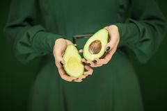 Woman in green dress hands holding some avocados. Sensual studio shot can be used as background Stock Images