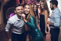 A woman in a green dress is singing songs with her friends at a karaoke club. Her friends have fun on the background. Royalty Free Stock Image
