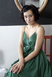Woman in green dress sitting on chair in bedroom Royalty Free Stock Images