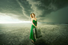 Woman in green dress with suitcase standing alone in the middle of the desert stock photography