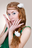 Woman in green dress touching her face Stock Photo