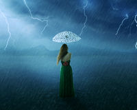Woman in green dress under umbrella on countryside flooded field Stock Image