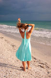 Woman in green dress walking along beach. In the gulf of mexico with waves crashing as she fixes her hair Stock Photography