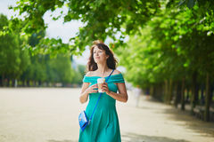 Woman in green dress walking with coffee to go in Tuileries garden of Paris, France Royalty Free Stock Image