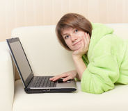 Woman in green dressing gown on sofa with laptop Royalty Free Stock Photo